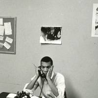 Ivanhoe Donaldson sitting behind a large desk covered with documents, he's on the phone and is holding his head in his hand